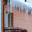 Overhanging icicles on the house roof over balconies — Stock Photo #21257475