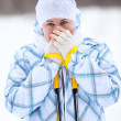 Attractive Caucasian woman warming frozen hands with ski poles in winter — Stock Photo #21257503