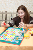Happy Caucasian young female playing board games in domestic room — Stock Photo