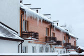Overhanging icicles on the house roof over balconies — Stock Photo
