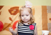 Little Caucasian with fork in hand in domestic room — Stock Photo