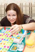 Caucasian young woman playing board games in domestic room — Stock Photo