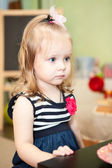 Cute young child sitting at the table in domestic room — Stock Photo