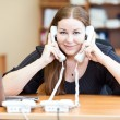 Tired executive business woman with two telephone handset calliing in office — Stock Photo