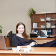 Woman resting with coffee mug on working place with legs on the table — Stock Photo #22263761