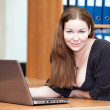 Attractive joyful Caucasian woman laying on the desk with laptop — Stockfoto