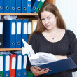 Attractive business woman with documents folder in hands at office — Stock Photo