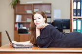 Happy joyful Caucasian woman laying on the desk with laptop in front — Stock Photo