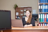 Beauty Caucasian woman in office interior with laptop at the desk — Stock Photo