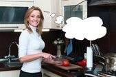 Beautiful happy smiling woman in kitchen interior cuts a tomato — Stock Photo
