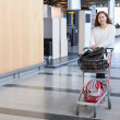Young Caucasian woman pulling luggage hand-cart in airport hall — Stock Photo