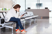 Tired Caucasian woman with devices sitting in airport lounge — Stock Photo