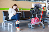Young Caucasian woman sitting with luggage hand-cart in airport lounge — Stock Photo