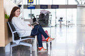 Happy smiling Caucasian woman with devices sitting in airport lounge — Stock Photo