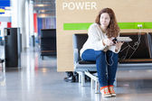 Thoughtful woman with electronic devices near place to charge your phone — Stock Photo