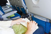 Caucasian female sitting in aircraft with boarding passes in hands — Stock Photo