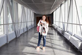 Young woman with mobile phone standing in airport hall — Stock Photo