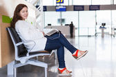 Smiling woman with devices sitting in airport lounge — Stock Photo