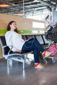 Woman dreaming with tablet pc in airport lounge with luggage hand-cart — Stock Photo