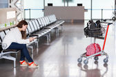 Spending time in airport lounge with luggage hand-cart — Stock Photo