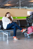 Tired woman looking at tablet pc in airport lounge with luggage hand-cart — Stock Photo