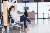 Transit passenger with devices waiting flight in airport lounge — Stock Photo