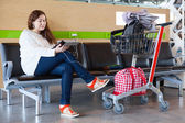 Woman looking at tablet pc in airport lounge with luggage hand-cart — Stock Photo