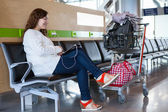 Woman spending time with tablet pc in airport lounge with luggage hand-cart — Stock Photo