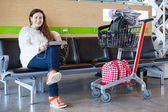 Happy young Caucasian woman sitting with luggage hand-cart in airport lounge — Stock Photo
