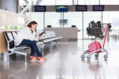 Tired woman waiting flight in airport lounge with luggage hand-cart — Stock Photo