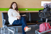 Serene woman charging tablet pc in airport lounge with luggage hand-cart — Stock Photo