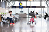 Woman waiting flight in airport lounge with luggage hand-cart — Stock Photo