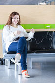 Happy woman charging her electronic devices in place to charge — Stock Photo