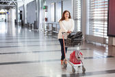 Young Caucasian woman pulling luggage hand-cart with bags along airport hall. Passenger in waiting area. — Stock Photo