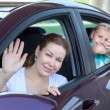 Happy Caucasians mother and young daughter waving from car windows — Stock Photo #27511191