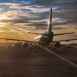 Passenger aircraft riding on runway in sunset sunlights — Stock Photo
