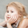 Thoughtful little Caucasian girl resting supporting his head by hands — Stock Photo #27511245