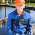 Senior manual worker sitting near water filtration unit — Stock Photo #27511249
