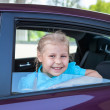 Happy Caucasians little girl smiling of a car — Stock Photo