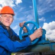 Caucasian mature worker with fitting valve against blue sky — Stock Photo