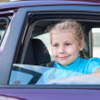 Happy smiling Caucasian girl looking through the car window — Stock Photo