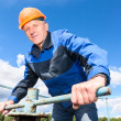 Mature Caucasian worker in a hardhat at the factory with the pipe valve — Stock Photo