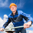 Senior Caucasian worker in a hardhat at the factory with the pipe valve against blue sky — Stock Photo