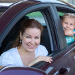 Happy Caucasians mother and young daughter looking at camera from car windows — Stock Photo #27511409