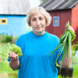 Caucasian woman with onion and lettuce standing against country house — Stock Photo