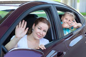 Happy Caucasians mother and young daughter waving from car windows — Stock Photo