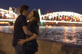 Romantic couple kissing near the river at night — Stock Photo