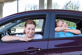 Caucasians mother and young daughter look out from car windows — Stock Photo
