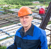Portrait of senior Caucasian manual worker standing against water treatment plant — Stock Photo