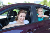 Caucasians mother and young daughter looking at camera from car windows — Stock Photo